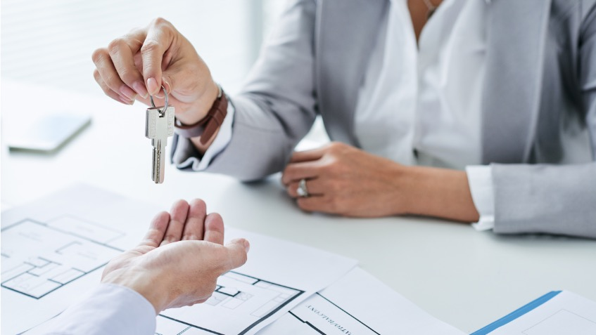 An estate agent hands over the key to a house. A floor plan of the property is on the desk.