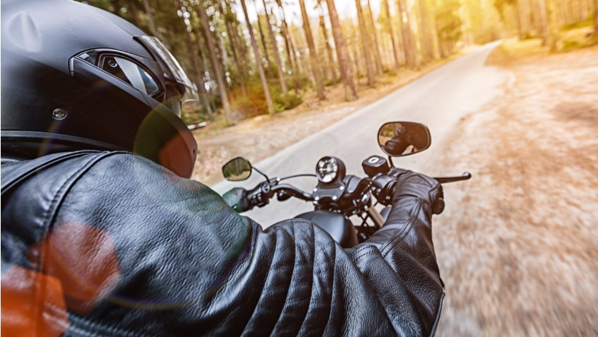 A motorcycle rider sits on his motorbike and looks ahead down an open road through the forest.