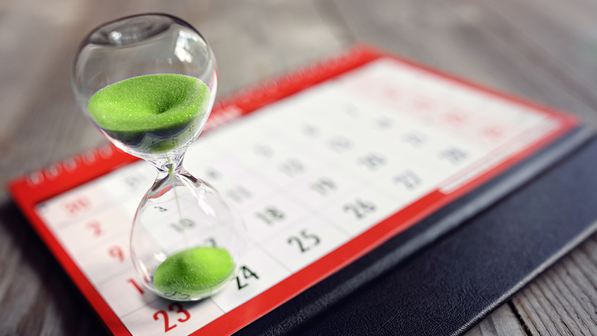 An hour glass standing on a calendar. The clock is ticking: It is never too early to start your private pension plan.