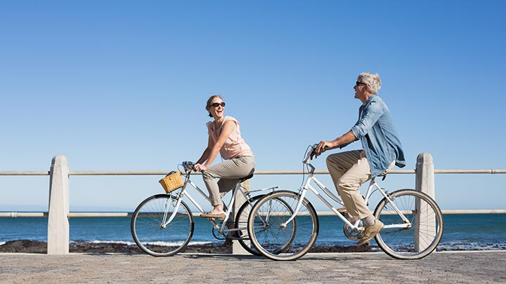 Couple riding bikes along the lakeside. Compare personal liability insurance and find the best premium with Comparis.